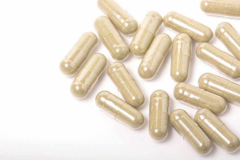 Herbs capsules on white background
